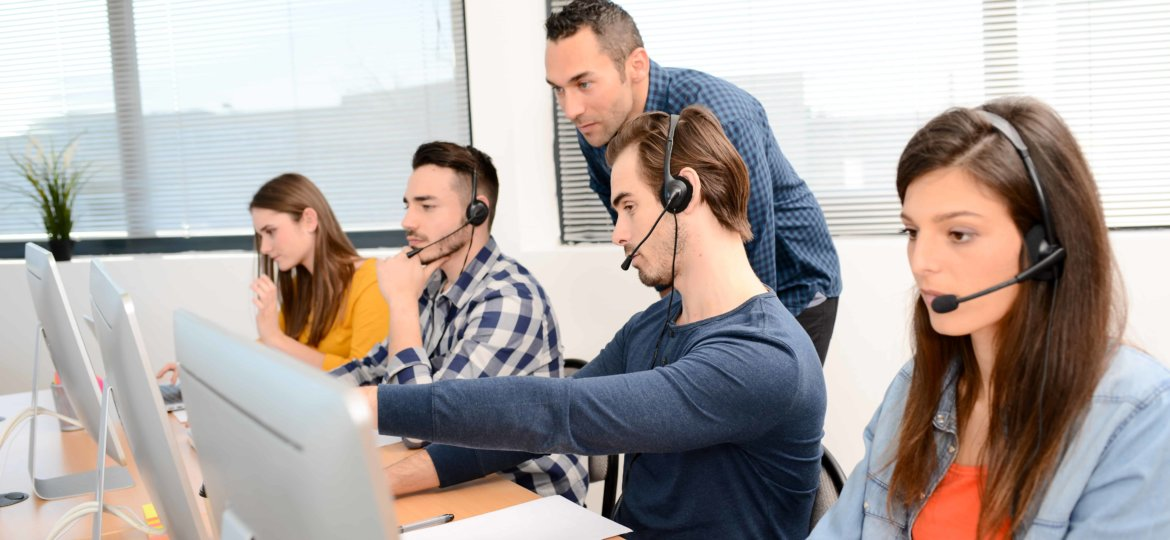 group of four young people with desktop computer in row and headset training with teacher instructor in customer service call support helpline business center